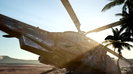 wwii : old rusted military helicopter in the desert at sunset