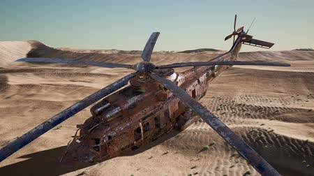 crashed : old rusted military helicopter in the desert at sunset