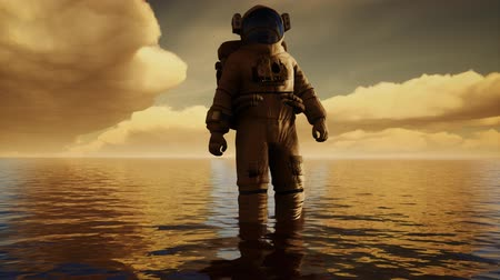 surrealista : Astronauta en el mar bajo las nubes al atardecer Archivo de Video