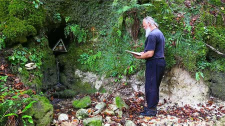 ascetic : The old pilgrim read the prayer at holy spring