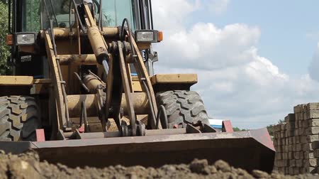 bagger : Digger shovels sand, roadworks Stock Footage