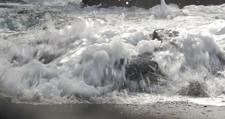 beach panorama : 4K, Dramatic water waves splashing and crashing against rocks, fisherman in front