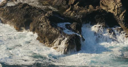 tempestade : 4K, Dramatic water waves splashing and crashing against rocks, fisherman in front