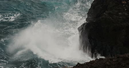 oceano : 4K, Dramatic water waves splashing and crashing against rocks, fisherman in front
