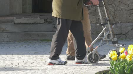 elderly man is walking with a walking frame