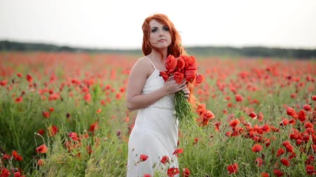 inspiradora : beautiful young woman in poppy field holding a bouquet of poppies