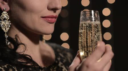 espumante : woman drinking champagne from a glass on a background of celebratory lights at night Vídeos