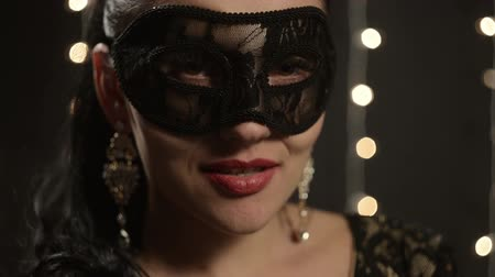 маскарад : woman in a Venetian mask on the background of night lights, close-up