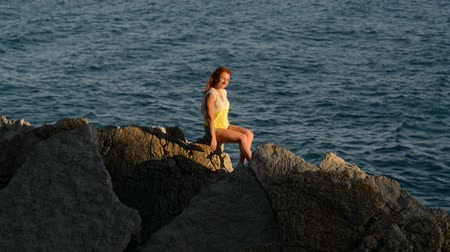 rocks red : Young red-haired woman with flying hair sitting on a rocky seashore, slow motion Stock Footage