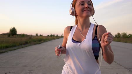 alívio : young woman runs and listens to music on headphones on a summer afternoon at sunset, close-up