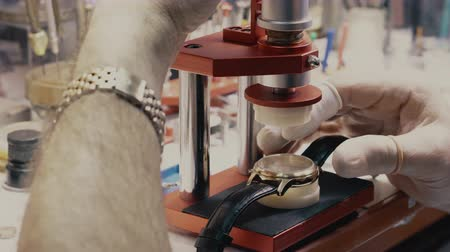 substituição : watchmaker replaces the glass in a wristwatch, close-up