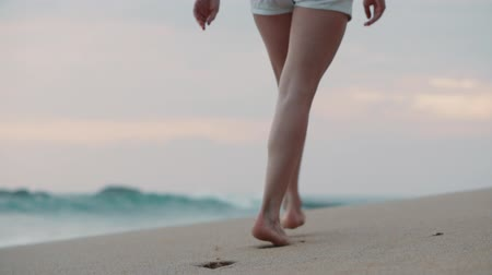 step : female legs go along the beach along the ocean, close-up
