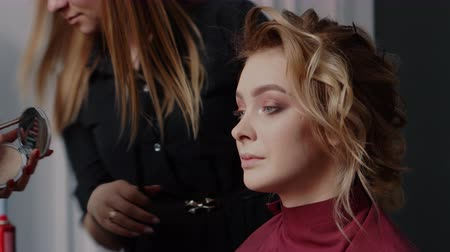 pulverização : make-up artist and hairdresser serve a woman in a beauty salon, close-up Stock Footage