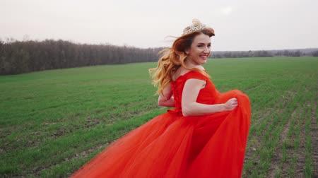 beatiful : young woman in a luxurious red dress runs along the green grass, rear view, slow motion