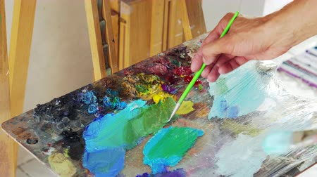 expo : artist stirs paint brush before drawing painting, close up