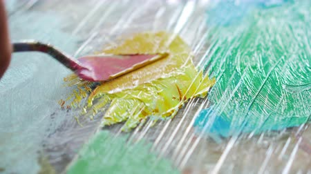 palette knife : artist stirs paint palette knife before drawing painting, close up