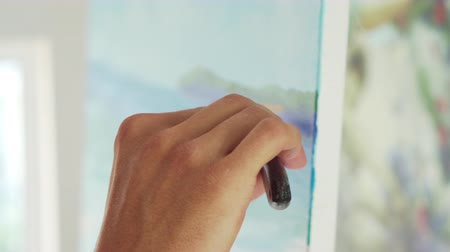 palette knife : artist draws palette knife on canvas, close-up of hand