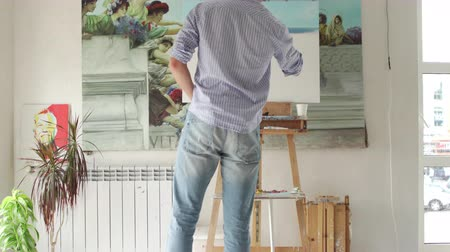muse : male artist paints picture on easel in art studio, rear view