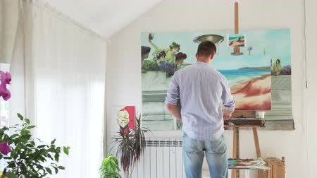 nowoczesne : male artist paints picture on easel in art studio, rear view