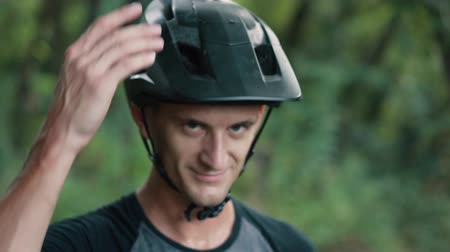 фиксация : man cyclist knocks his hand on helmet on his head