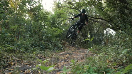 enduro : mountain biker rushes along road in forest