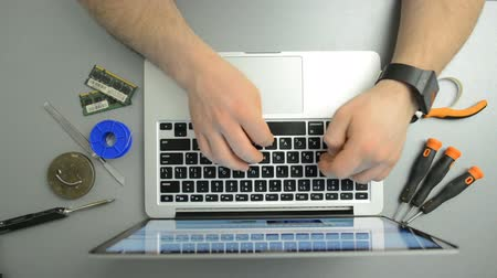 inventing : Man typing text on the laptop keyboard in the service center