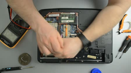 computer programmer : The engineer dismantles the laptop for repair