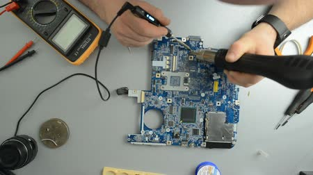 inventing : Engineer soldering the computer motherboard, top view