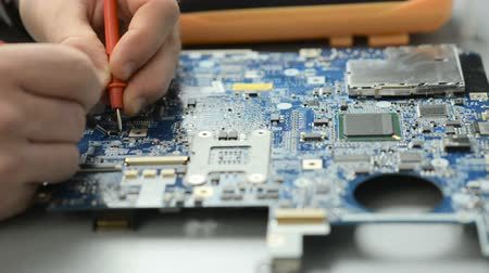 inventing : The engineer repairs the computers motherboard in the service center