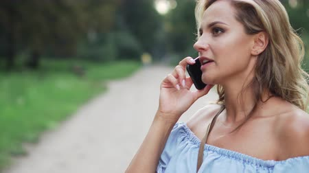 annoyance : angry blonde talking on phone Stock Footage