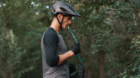 enduro : cyclist drinks water through tube Stock Footage