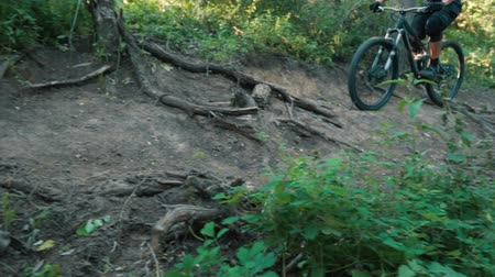 enduro : man cyclist rides off-road in forest, close-up