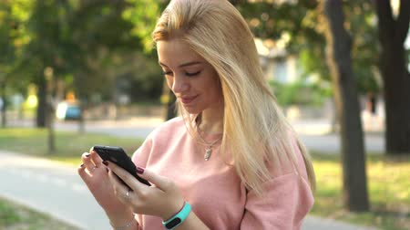 blond vlasy : girl is using smartphone on street
