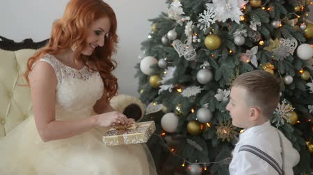 świecznik : young beautiful mother and son consider Christmas gifts on the background of Christmas decorations