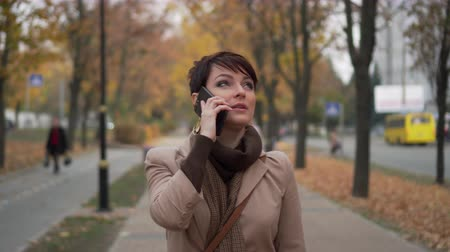 sikátorban : stylish woman is having fun talking on phone on background of autumn city