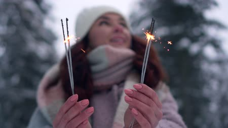 jiskry : close-up of female hands holding burning sparklers