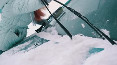 soğuk : woman removes snow from windshield of car Stok Video