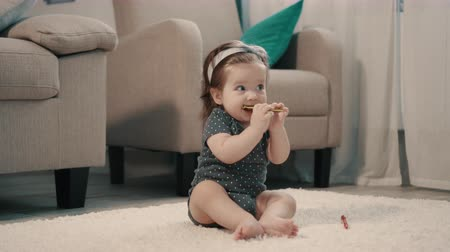 genuíno : Baby girl nibbles toy while sitting on floor at home Vídeos