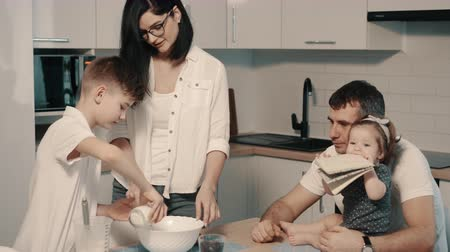 qualidade : Young happy family cooking dinner together in kitchen Stock Footage