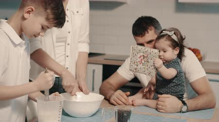 qualidade : Young family preparing food in kitchen at home