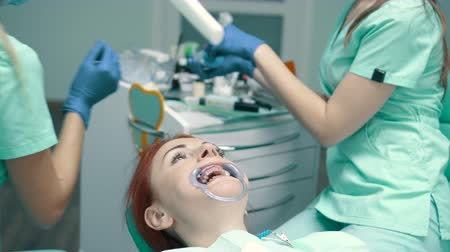 branqueamento : Young woman sits in chair at reception at dentist Stock Footage