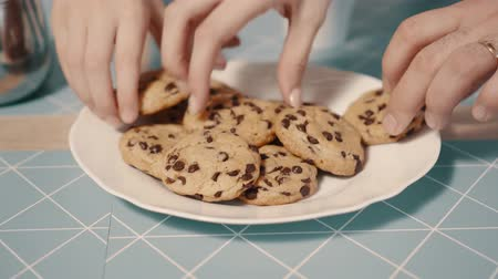 megragad : Hands take fresh cookies from plate, close-up Stock mozgókép