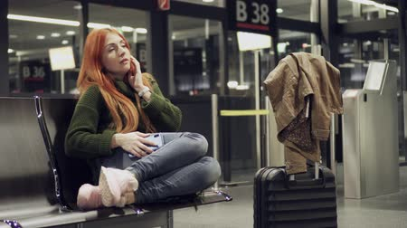 časová prodleva : Female is waiting for delayed flight at night airport.