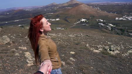 топ : Young woman is by hand of his companion on mountain top