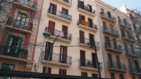BARCELONA, SPAIN - FEBRUARY 19, 2019: view of facades of buildings on streets of city, Catalan flags on balconies Stock Footage