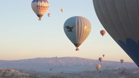 GOREME, TURKEY - NOVEMBER 1, 2018: colorful hot balloons fly over rocks