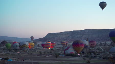 GOREME, TURKEY - NOVEMBER 1, 2018: llots of colorful balloons start flying up over valley