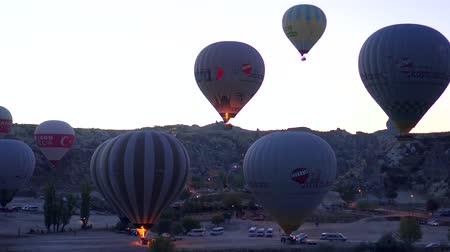 GOREME, TURKEY - NOVEMBER 1, 2018: llots of colorful balloons start flying up over valley in predawn twilight