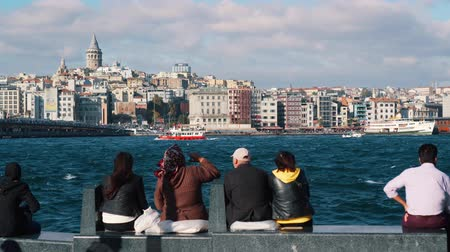 турецкий : ISTANBUL, TURKEY - NOVEMBER 4, 2018: people sit on waterfront and look at Bosphorus