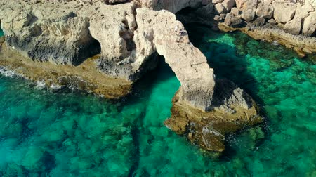 arch bridges : Aerial view of Lovers Bridge on rocky shore of Mediterranean, Cyprus Stock Footage